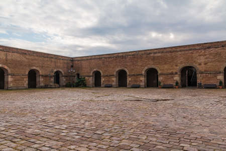 Barcelona, Catalonia, Spain - November 16, 2018: The courtyard of the Montjuic Castle with pavement, stone walls and arches in cloudy day