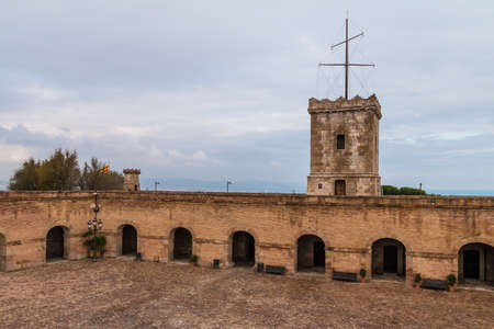 Barcelona, Catalonia, Spain - November 16, 2018: The tower and the courtyard of the Montjuic Castle with pavement, stone walls and arches in cloudy day Editorial