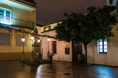 Barcelona, Catalonia, Spain - November 17, 2018: Beautiful night view of an illuminated square, buildings and tangerine tree in the open-air Poble Espanyol architectural museum Editorial