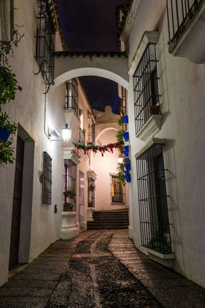 Barcelona, Catalonia, Spain - November 17, 2018: Beautiful night view of an illuminated narrow street and buildings in the open-air Poble Espanyol architectural museum