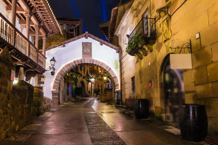 Barcelona, Catalonia, Spain - November 17, 2018: Beautiful night view of an illuminated street and buildings in the open-air Poble Espanyol architectural museum Editorial