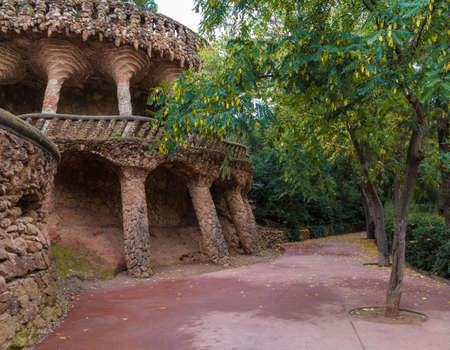 Barcelona, Catalonia, Spain - November 18, 2018: Beautiful view of the stone viaduct and footpath with bushes and trees in the Park Guell in overcast autumn day