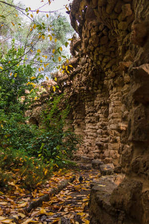 Barcelona, Catalonia, Spain - November 18, 2018: Beautiful view of the stone viaduct and lush vegetation in the Park Guell in overcast autumn day Editorial