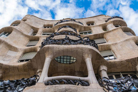 Barcelona, Catalonia, Spain - November 19, 2018: Worm's-eye view of Casa Mila on the background of cloudy sky. The building designed by Antonio Gaudi in the years 1906-1910. Editorial