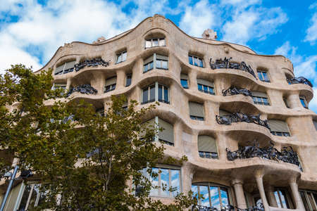 Barcelona, Catalonia, Spain - November 19, 2018: Low-angle view of Casa Mila on the background of cloudy sky. The building designed by Antonio Gaudi in the years 1906-1910. Editorial