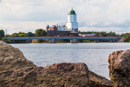 A boulder on the coast of Gulf of Finland on the background of the Vyborg Castle on overcast day, Vyborg, Leningrad Oblast, Russia