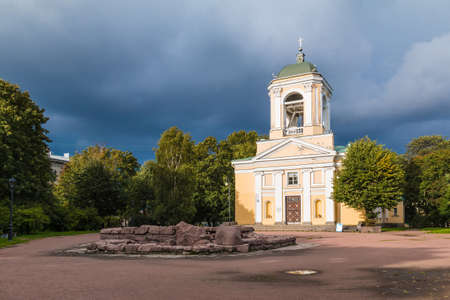 The Church of the Saints Peter and Paul illuminated by the sun on the background of trees and a thunderclouds, Vyborg, Leningrad Oblast, Russia
