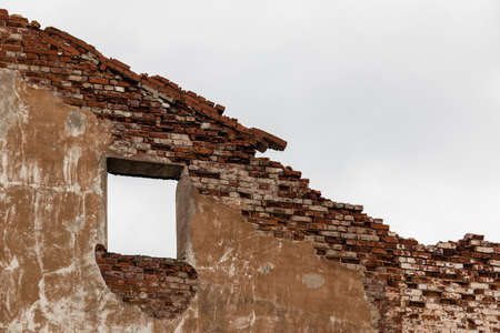 A dilapidated brick wall with a window hole on the background of overcast sky Banco de Imagens