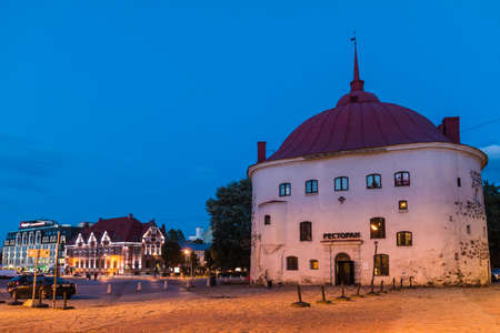 Vyborg, Leningrad Oblast, Russia - September 12, 2018: Beautiful view of the illuminated Market Square and the Round Tower at twilight Editorial