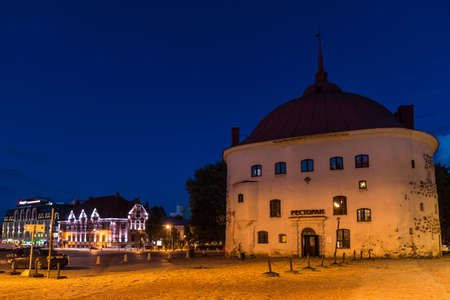 Vyborg, Leningrad Oblast, Russia - September 12, 2018: Beautiful view of the illuminated Market Square and the Round Tower at dusk