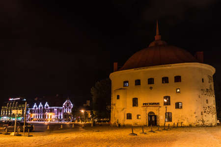 Vyborg, Leningrad Oblast, Russia - September 12, 2018: Beautiful view of the illuminated Market Square and the Round Tower at night