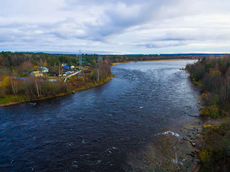 Drone view of the Vuoksi river, the forest and the settlement in autumn day, Losevo, Leningrad Oblast, Russia