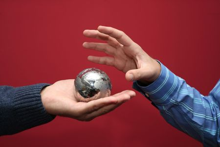 Hand grabbing a small planet puzzle globe. World concept Stock Photo - 2831785