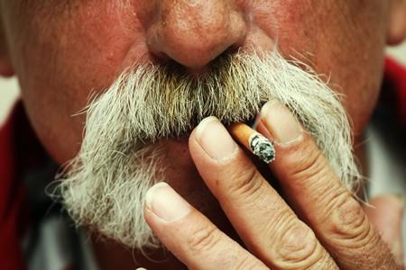 Man smoking a cigarette. Big cowboy style moustaches photo