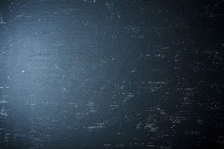 Blue spotlight light on black grunge wall. Can be used as background texture photo