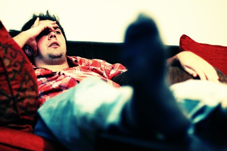 lying on couch: Lazy man chilling out on sofa watching tv Stock Photo