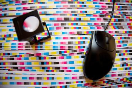 prepress: Rat�n del ordenador y la impresi�n lupa, se centran en las tiras CMYK. Prepress color menagement en concepto de impresi�n de producci�n.