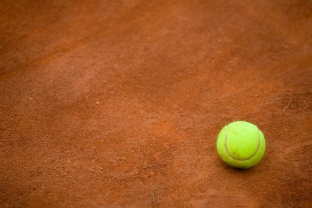 Detail of clay tennis court with Tennis ball. Useful for tennis background designs