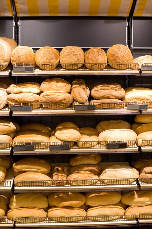 unsliced: Bakery Store shelves full of various bread.