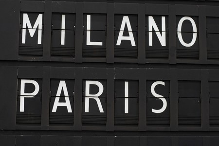 scheduled: Flights info board on airport concept. Fashion cities Paris and Milano Stock Photo