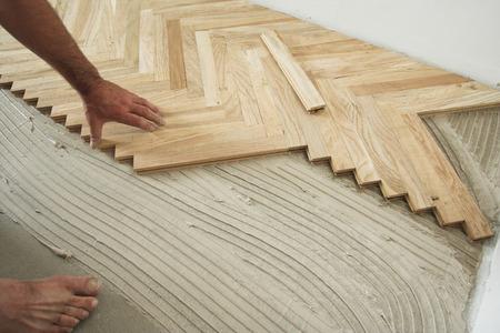 Carpenter on work putting wood floor - parquet pieces. Home construction concept photo