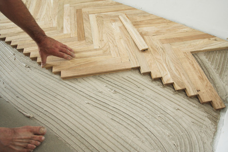 Carpenter on work putting wood floor - parquet pieces. Home construction concept