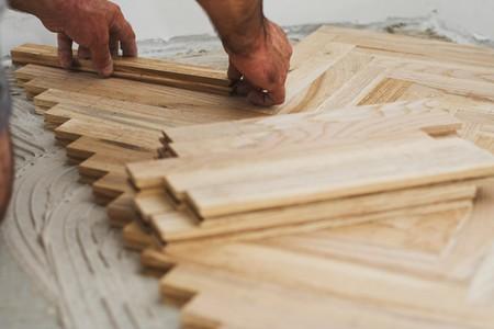 Carpenter on work putting wood parquet pieces. Home construction Standard-Bild
