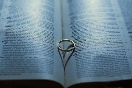 Resumen en forma de coraz�n hermosa sombra de un anillo de boda en un libro de amor de fondo. Foto de archivo - 4421367