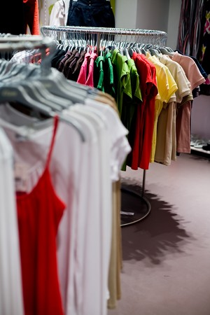 Clothes hangers with shirts in colors in store ready to buy. Fashion shopping concept photo