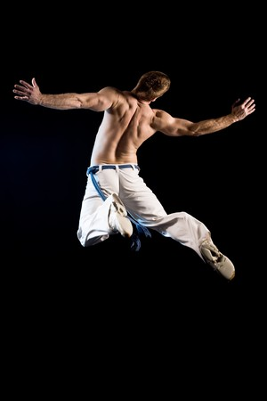 Man in the air from behind. Jump from explosion pose Stock Photo
