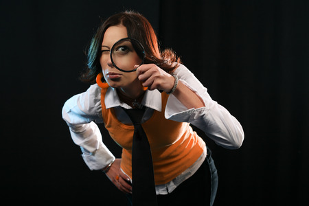 Young woman holding magnifying glass like detective. Investigation concept on black