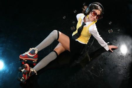 Funky girl with rollerskates and headphones isolated on black disco dancefloor, enjoy Stock Photo - 4406051
