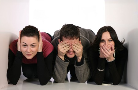 censor: Three young people in small space covering ears, mouth and eyes. communication concept Stock Photo