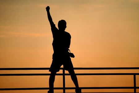 raised hand: Silhouette of jumping man. victory concept. Happy man with raised hand Stock Photo