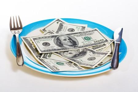 negocios comida: El dinero en el plato con un tenedor, cuchillo y cuchara. Econom�a y negocios concepto Foto de archivo