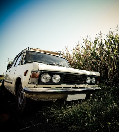 Retro car by the road. Old grunge style vehicle photo