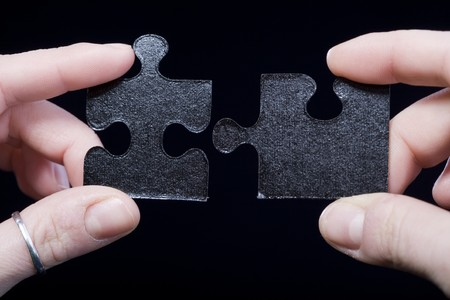 Hands trying to connect two puzzle piece isolated on black. Partnership concept Stock Photo - 4422047