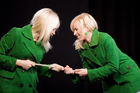 Tug of War between two twin sisters. duel and challenge concept photo