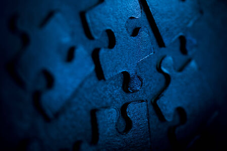 Neon blue jigsaw parts on dark background. Puzzle concept