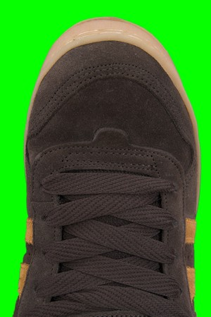 lacing sneakers: Close up of urban sneakers. Brown sneakers isolated on green