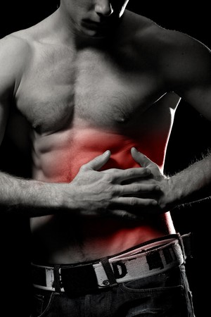 Man holding his ribs and stomach in pain. Medical concept photo