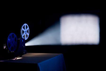 movie pelicula: Antiguo proyector de cine de origen, funcionamiento y proyecci�n de la pel�cula en blanco en una pantalla con el haz de luz visible Foto de archivo