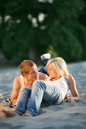attractive young couple laying together on sand beach at sunset photo