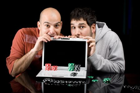 Two gamblers addicted to online gambling, with computer and chips expecting results Stock Photo