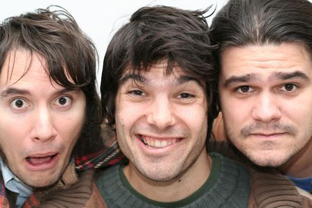 Close-up face of three funny menmaking faces and having fun