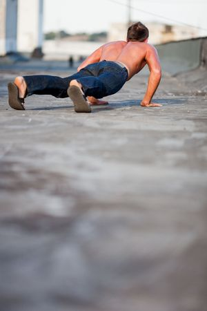 pushup: Young handsome man doing pushup on rooftop