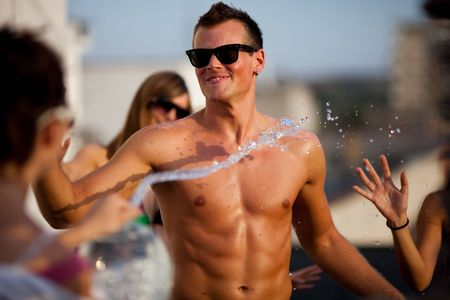 Young people having fun on summer vacation. Girl splashing boyfriend with water photo