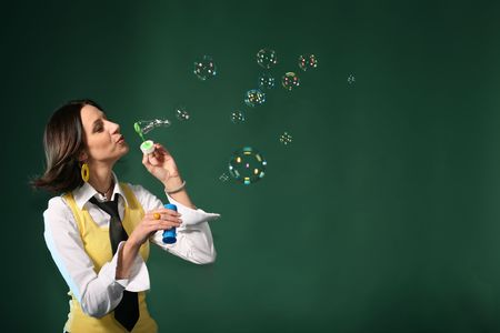 Woman making soap bubbles on green background with copy space. Happy lifestyle concept photo