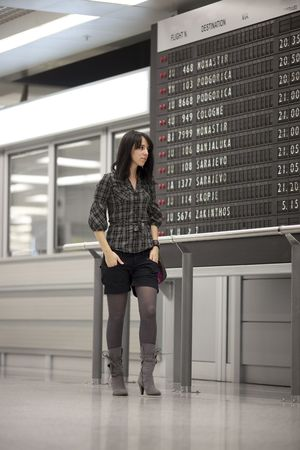 scheduled: Lone girl waiting at the airport and looking at the scheduled arrivals board. Some noise visible Stock Photo