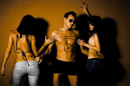 threesome: Portrait of jealous people. Handsome man in between two sexy woman